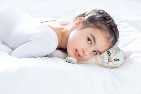 Portrait of a beautiful little girl in white clothes, lies on a clean, white bed with a white British cat.