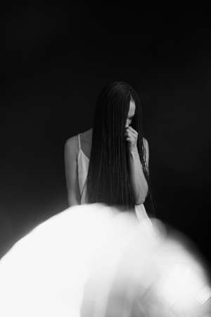 Surreal black and white portrait of a girl with a glass ball, play of light and shadow, fashion art photography Standard-Bild