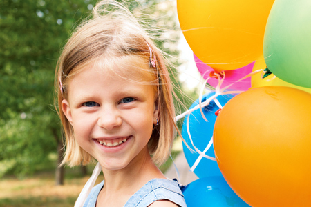 smiling girl with balloons on the street in the summer photo