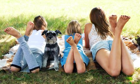 pies descalzos: niños felices acostado en la hierba verde al aire libre en la hierba con el perro