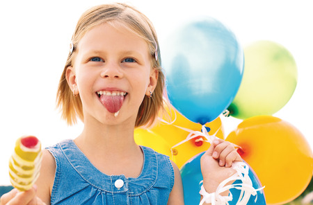 Girl licking ice cream and holding a balloons photo