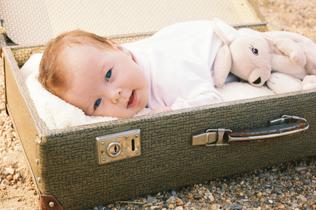 Baby lying in a suitcase with a toy photo