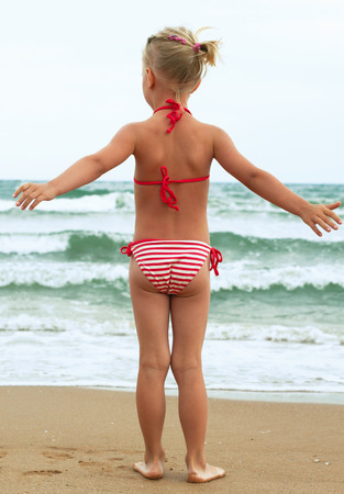 The little girl is going to swim in the sea photo
