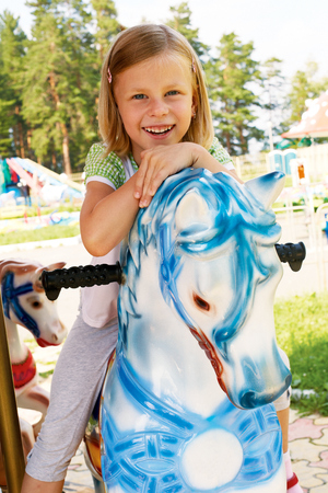 playground rides: cute little girl riding on a carousel in an amusement park in the summer Stock Photo