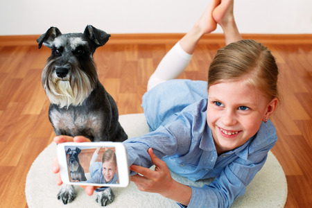miniature dog: little girl taking photo of herself and her dog with mobile phone camera