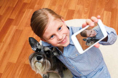 animal picture: little girl taking photo of herself and her dog with mobile phone camera