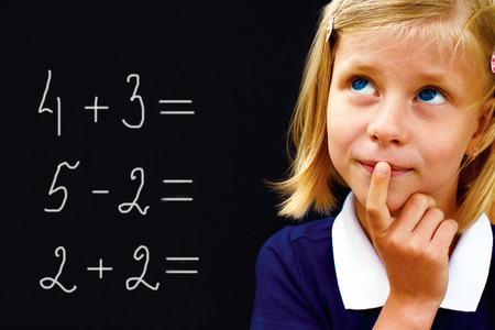 Portrait of a little happy pretty schoolgirl doing arithmetic on blackboard in class and smiling