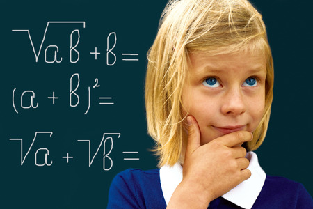 arithmetic: Schoolgirl ponders solving a mathematical problem standing at the blackboard  Stock Photo