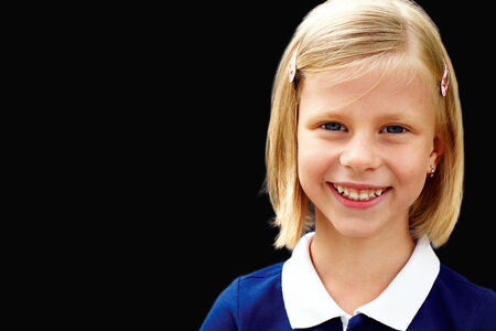 school room: Portrait of smart school child standing at chalkboard and looking at camera  Stock Photo