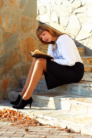 Student sitting on the steps and reading a book photo