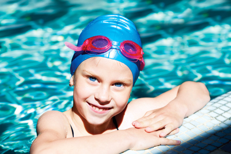 swimming suit: beautiful girl in a bathing suit, swim cap, goggles, holding on overboard in a swimming pool Stock Photo