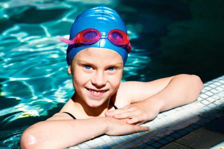 pool preteen: beautiful girl in a bathing suit, swim cap, goggles, holding on overboard in a swimming pool Stock Photo