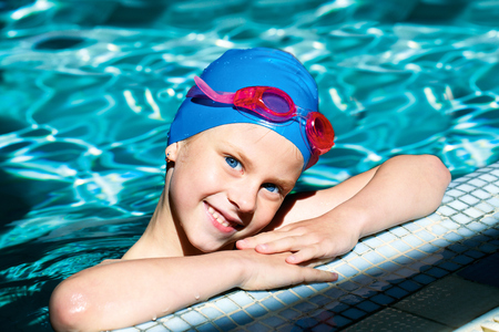 beautiful girl in a bathing suit, swim cap, goggles, holding on overboard in a swimming pool photo