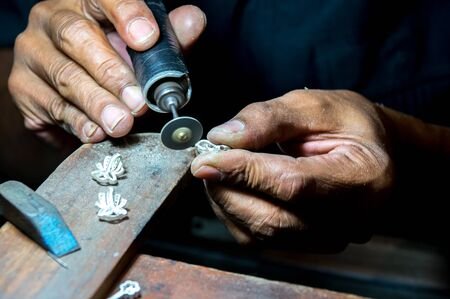 Close-up of making earrings by polishing a motor tool in a workshop Standard-Bild