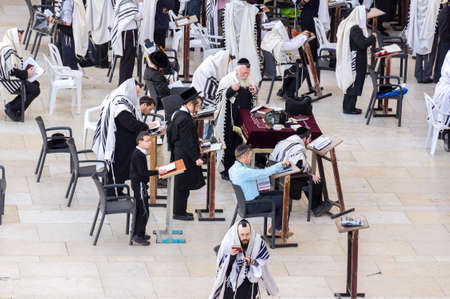 Jerusalem, Israel - 15/04/2015. Orthodox Jewish men pray at western wall in the morning
