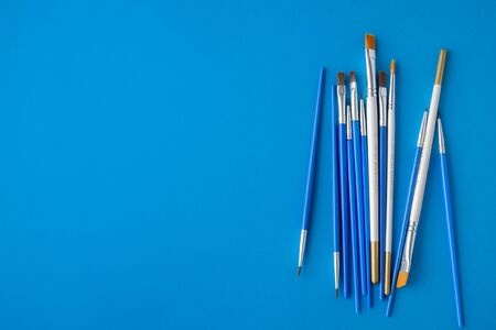 Flay lay, top view table desk. Set of different artist brushes on a blue background