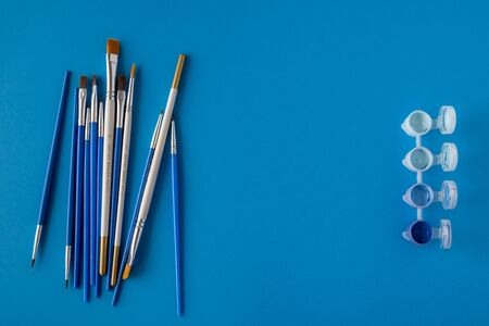 Flat lay, top view of the table. Set of different artist brushes and multi-colored paint for drawing in small banks on a blue background