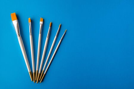 Flay lay, top view table desk. Set of different artist brushes on a blue background 版權商用圖片