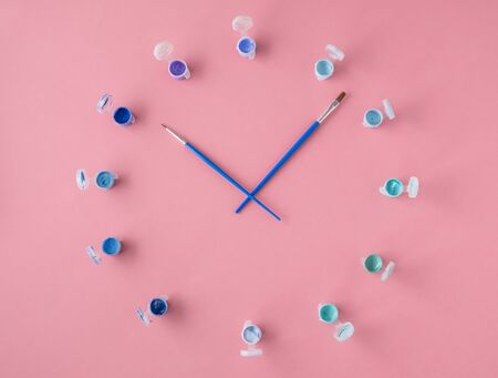 Flat lay, top view of the table. Clock from different colors and the artists brush in the form of arrows on a pink background