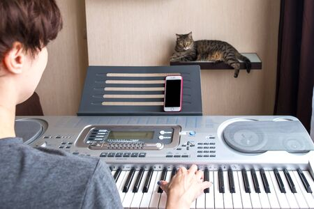 A woman is training to play the electric piano. The cat lies on a shelf and listens to it. Online piano lessons at home. Stay at home Foto de archivo