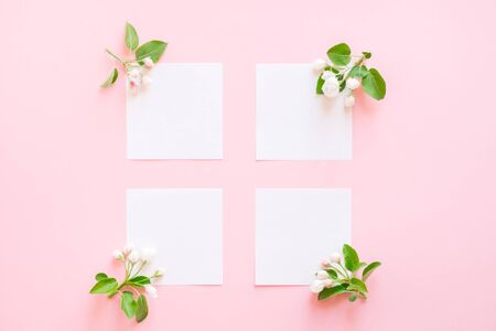 Summer and spring composition. Branch of a blossoming apple tree, white paper blank on pink background. Summer and spring concept. Flat lay, top view, copy space. Zdjęcie Seryjne