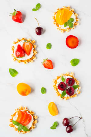 Top view of traditional Belgian waffles with soft cheese, fruits and berries. flat lay