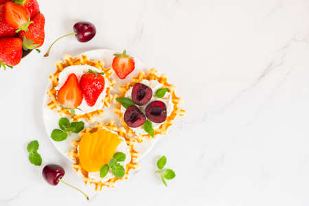 Top view of traditional Belgian waffles with soft cheese, fruits and berries with copy space Stockfoto