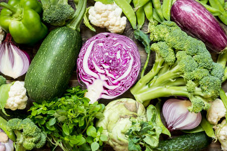 Top view set raw of green, red and purple vegetables spread on dark wooden background