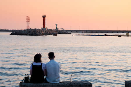 Couple watching the sunset by the sea, sochi, russia.