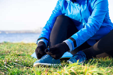 Woman tightening laces on sneakers, no face, preparing for outdoor workout in autumn in warm clothes. 免版税图像