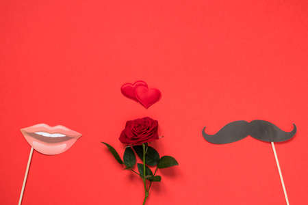 Valentine's day, love, romantic concept. Fresh red rose flower and red heart with mustaches and lips paper prop on red background.