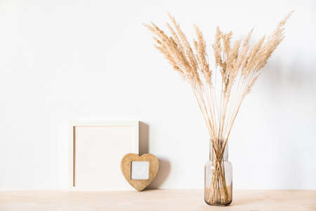 Dried flowers and a photoframes against a light wall in a minimalist style