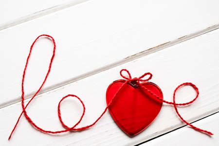 Valentine's day concept. Red heart and word love made from woolen rope on wooden background with copy space.