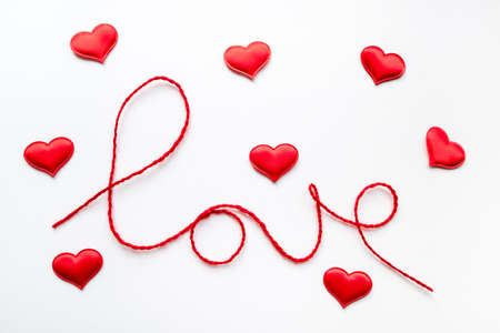 Valentine's day concept. Red heart and word love made from woolen rope on white background