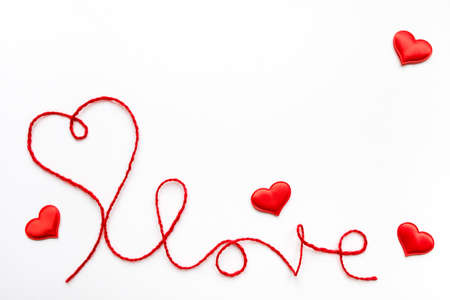 Valentine's day concept. Red heart and word love made from woolen rope on white background with copy space Stock fotó