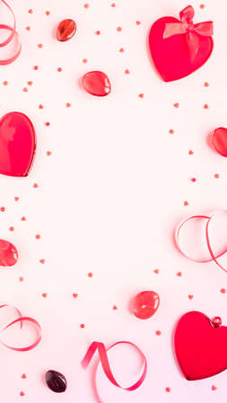 Valentine's day, love, romantic concept. Red hearts and ribbon on a pink background with copy space
