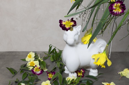 A white unicorns with lots of colorful spring flowers