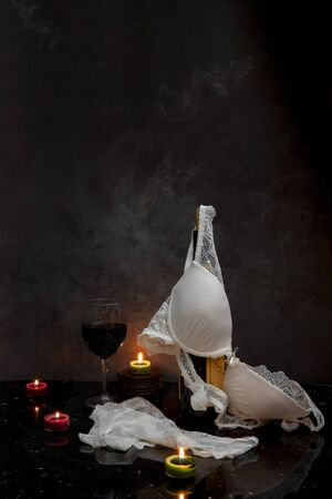 Still life with candles, lingerie and wine