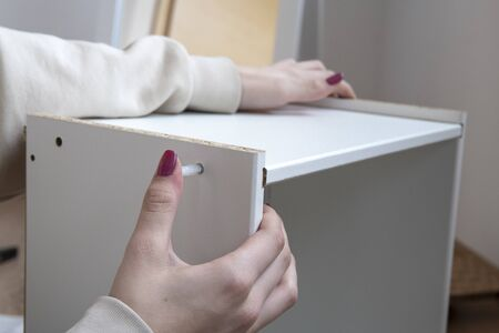 Woman hands with manicure assambling small cabinet