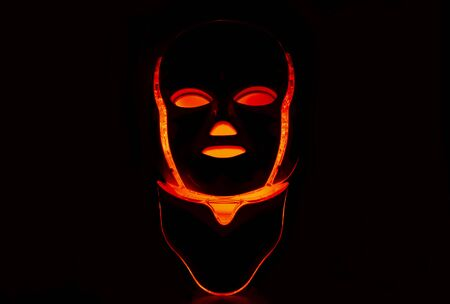 Led mask with neck glowing red on black background