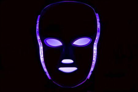 Led mask glowing purple on black background Stock Photo