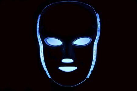 Led mask glowing blue on black background Stock Photo
