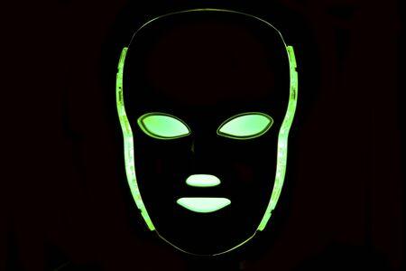 Led mask glowing green on black background Stock Photo