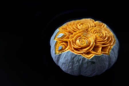 Green pumpkin with carved beautiful flowers on black background