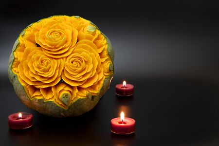 Beatiful carved pumpkin with flowers on black background
