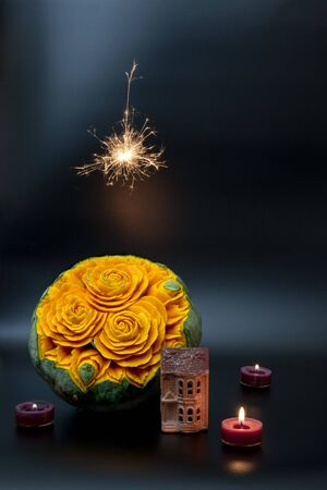 Beatiful carved with flowers pumpkin with a small house, candles and bengal lights on black background Stok Fotoğraf
