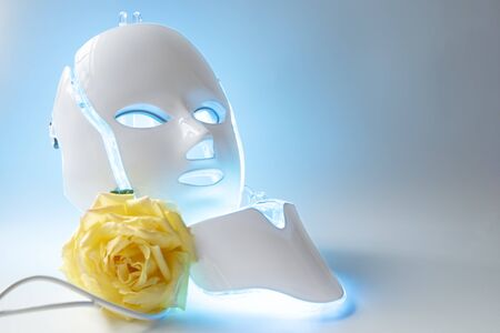 Color therapy mask glowing blue with yellow rose