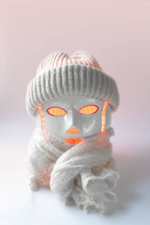 Color therapy mask glowing pink with knitted white hat and scarf