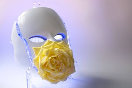 Color therapy mask glowing blue with yellow rose on pastel light oink and blue cacground