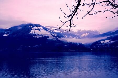 Lake, surraounded with with snow mountains and pink clouds Stok Fotoğraf